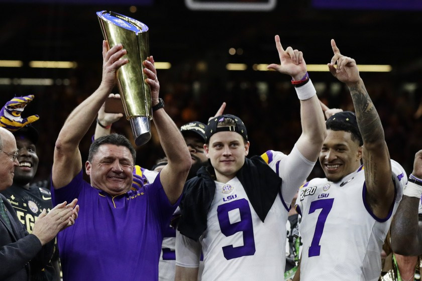 Louisiana State coach Ed Orgeron holds the trophy beside quarterback Joe Burrow, center, and safety Grant Delpit after beating Clemson in the College Football Playoff championship game in New Orleans.